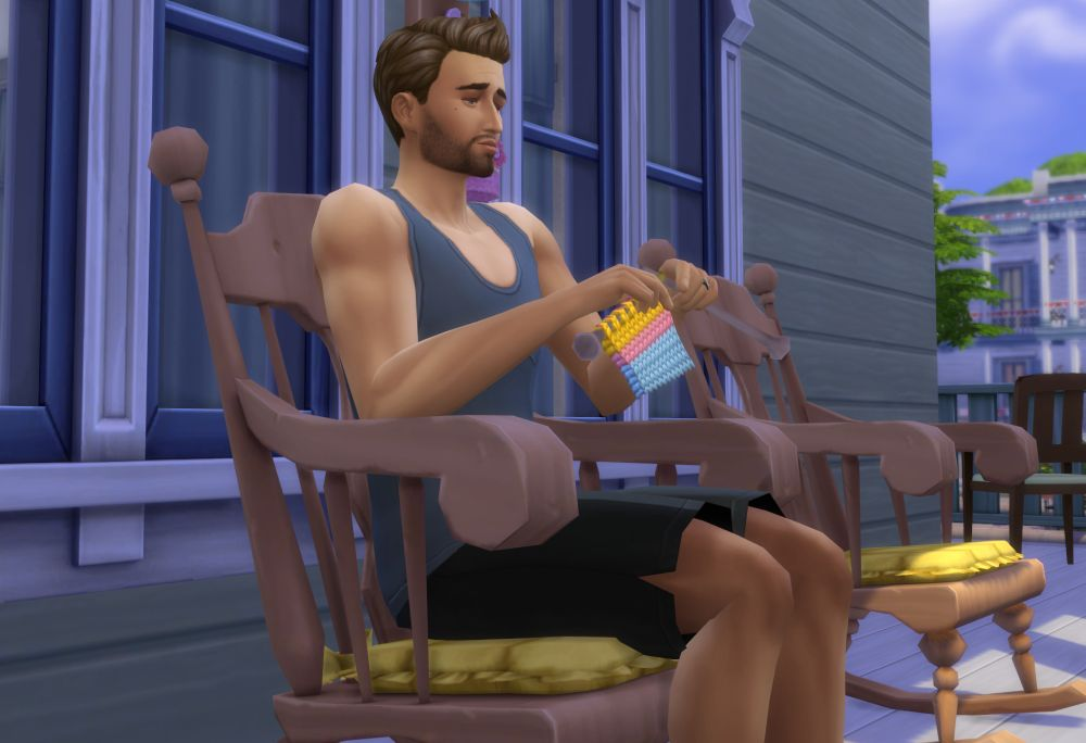 A Sim knits in a rocking chair in The Sims 4 Nifty Knitting Stuff Pack